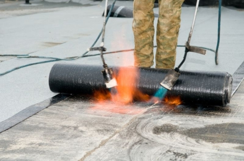 Roofing felt installation with heating and melting roll of bitumen roll by torch on flame
